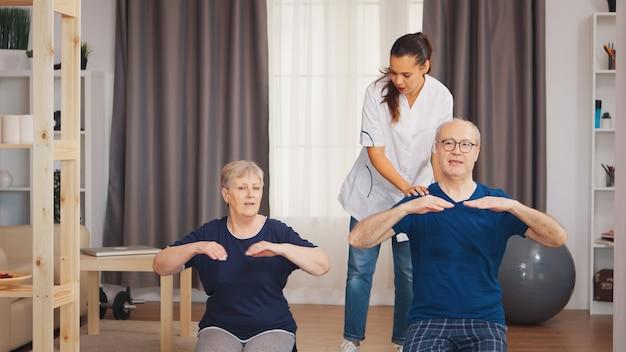 老夫婦の体力トレーニングを手伝う看護師。在宅支援、理学療法、老人の健康的なライフスタイル、トレーニング、健康的なライフスタイル