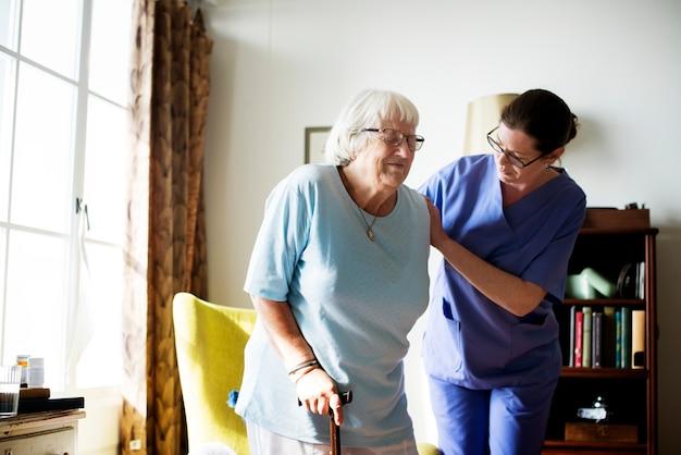 Медсестра помогает старшей женщине встать