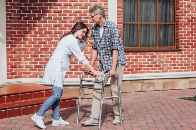 Медсестра помогает пожилому человеку в инвалидной коляске в доме престарелых