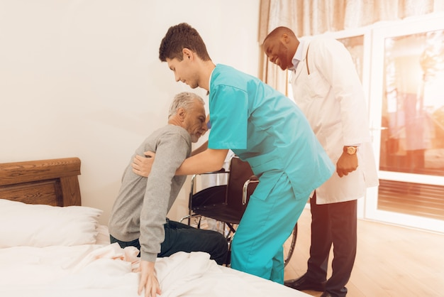 The nurse helps the elderly man to get out of bed.