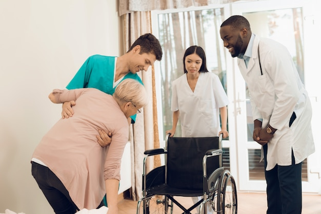 The nurse helps an elderly woman to get into a wheelchair