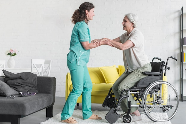 Nurse holding disabled senior woman's hand sitting on wheel chair