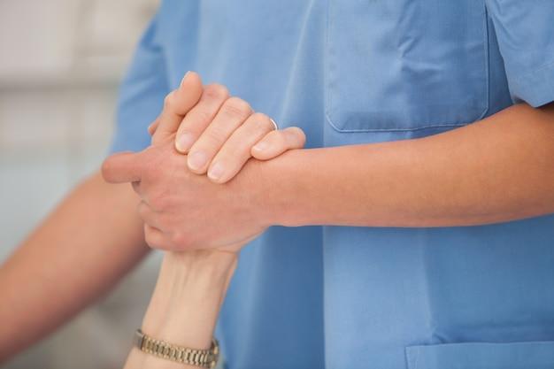 Nurse holding hands of the elderly lady