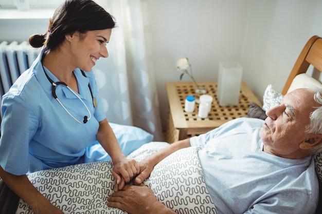 Nurse holding hands of senior man