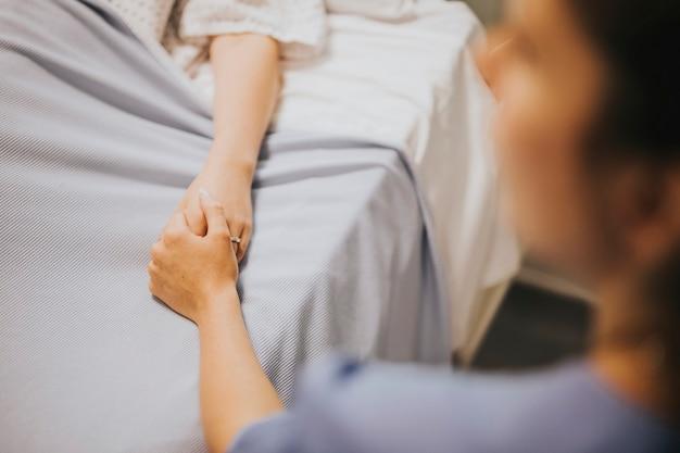 患者の手を握っている看護師