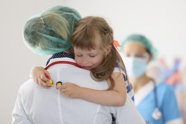 クリニックで目を閉じて小さな女の子を保持している看護師