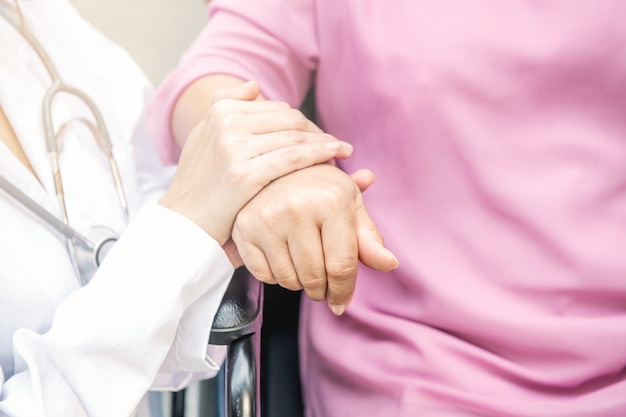 車椅子で古い女性の手を保持している看護婦