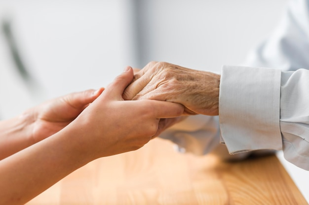 Nurse holding senior man's hands for comfort