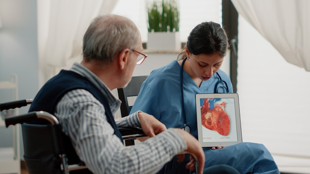 심장학 진단을 위한 심장 그림이 있는 태블릿을 들고 있는 간호사