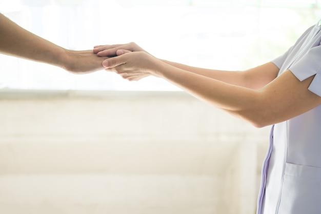 同情と優しさを示す、患者の男の手を握っている看護婦