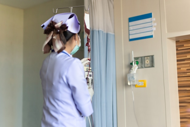 Nurse in hospital with blood products infusion of donor blood