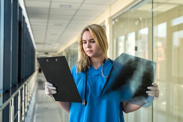 파란색 유니폼을 입은 간호사가 폐의 xray 필름에서 폐렴을 확인합니다. 코로나 19