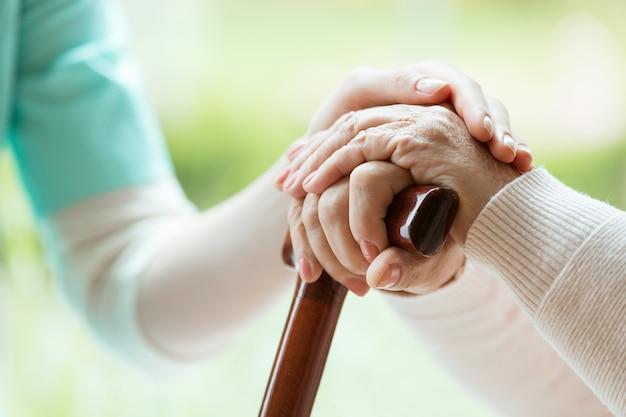 彼女の手に触れることによって老婦人を慰めるエプロンの看護師