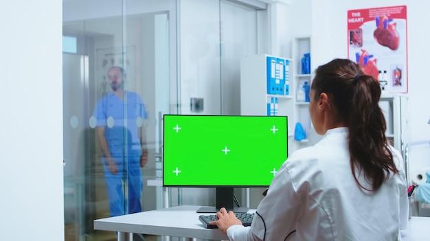 メディックが緑色の画面のモックアップを備えたコンピューターを使用しているときに、青い制服を着た看護師が病院のキャビネットに入る。