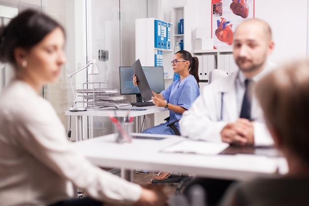 의사가 휠체어를 탄 장애인 노인 여성과 상담하는 동안 병원 사무실에서 엑스레이 이미지를 들고 파란색 유니폼을 입은 간호사. 건강 검진에서 젊은 여자와 그녀의 장애 어머니.