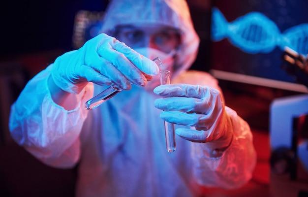 マスクと白い制服を着た看護師、液体でチューブを保持し、コンピューターとコロナウイルスワクチンを検索する医療機器を備えたネオン照明の実験室に座っている
