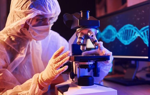 コンピューター、顕微鏡、コロナウイルスワクチンを検索する医療機器を備えたネオン照明の実験室に座っているマスクと白い制服を着た看護師