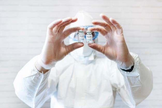 보호 복을 입은 간호사가 양성 표시가있는 covid 19 백신 유리 병을 카메라에 보여줍니다.