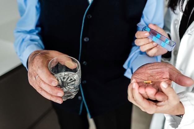 흰 코트를 입은 간호사가 물 한 잔을 들고 노인의 손에 알약을 놓습니다.