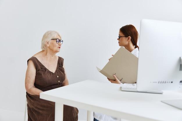 백의를 입은 간호사가 노인 여성 건강 관리에 대해 이야기하고 있습니다.