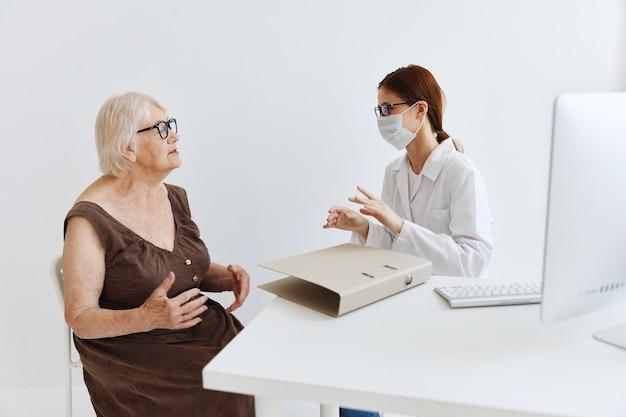 Медсестра в белом халате разговаривает с диагностикой здоровья пожилой женщины