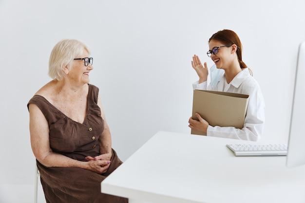 Медсестра в белом халате разговаривает с пожилой женщиной профессионального лечения