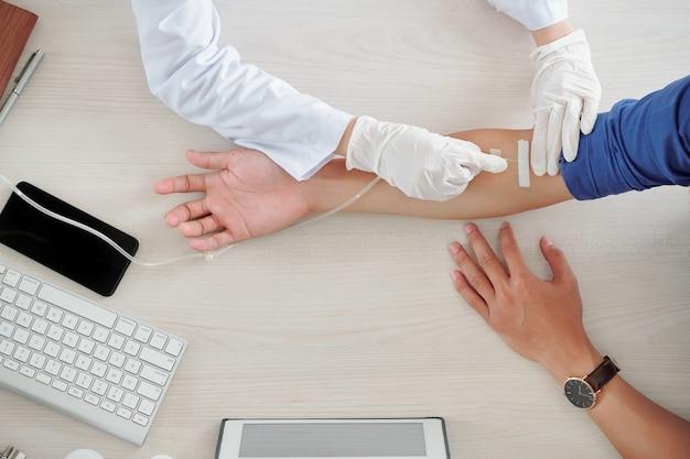 Nurse inserting needle with catheter