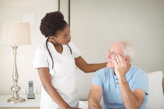 Nurse interacting with senior man on bed