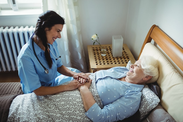 Nurse interacting with senior woman on bed