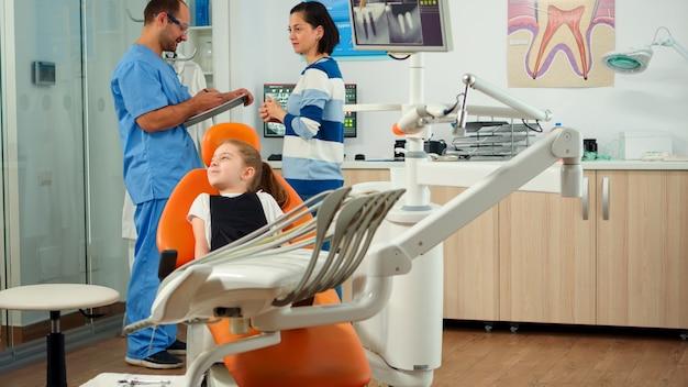 診察歯科室に子供患者を招待する看護師、小さな女の子と話す小児科医。歯科矯正医院で歯科矯正検査の準備をしている母親と話している男性アシスタント