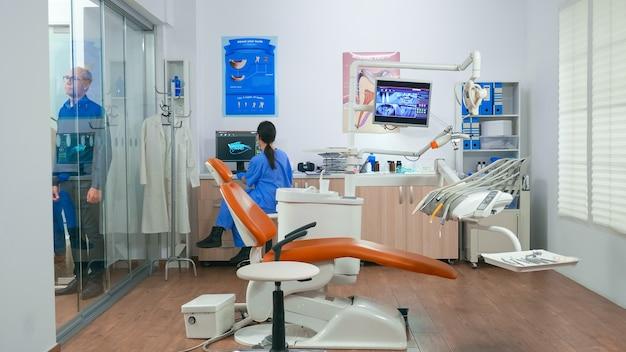 椅子に横になっていることを示す口腔病学室で次の患者を招待する看護師。医者がバックグラウンドで老人と話している間、年配の女性と相談歯科室に座っている歯科助手。