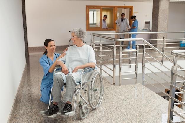 車椅子に座っている古い女性の横にひざまずいている看護婦