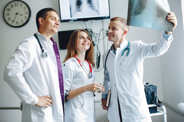 Медсестра слушает врача. студенты в больничных халатах. мужчины и женщины, стоящие в больничной палате.