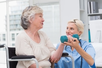 Nurse looking at patient while assisting her in lifting dumbbell