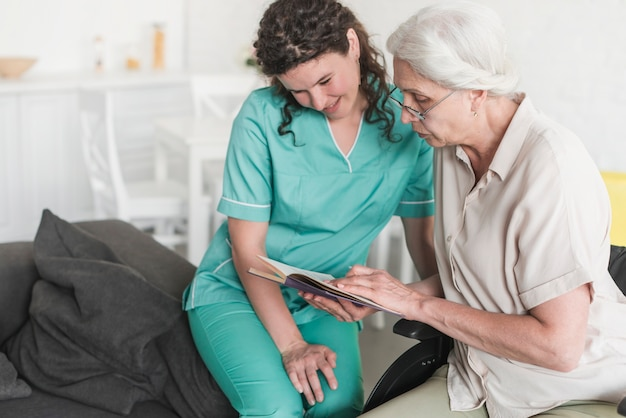 Nurse looking at senior woman reading book