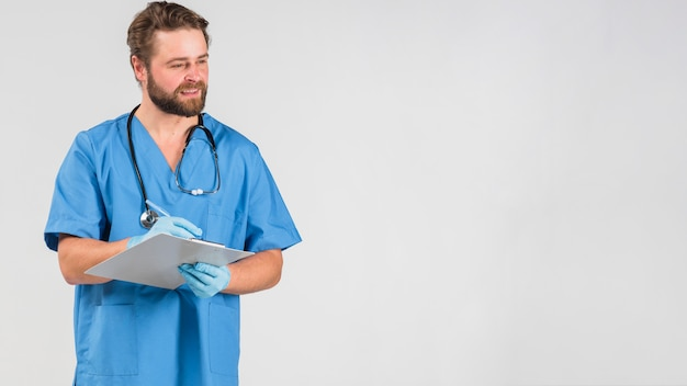 Nurse man holding clipboard and looking away