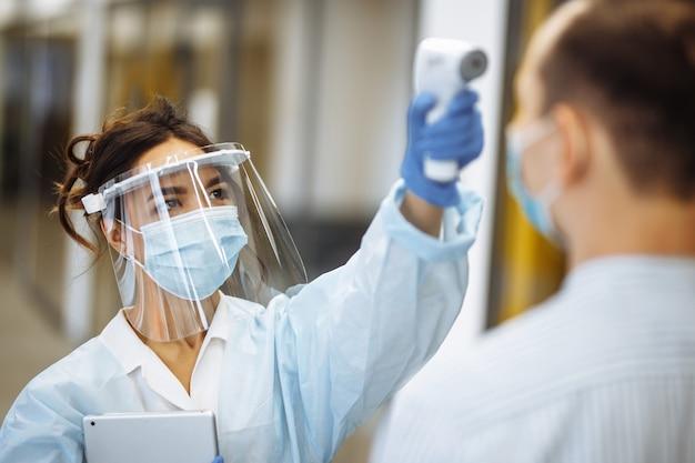 간호사는 비접촉 온도계로 환자 병원 방문자의 체온을 측정합니다. 보호 의료 마스크를 착용하는 사람들. 코로나 바이러스 예방 및 건강 관리 개념.