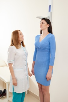 Медсестра измеряет рост молодой женщины в кабинете врача