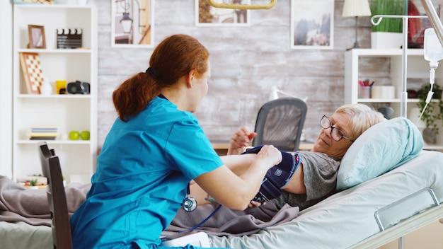 老人ホームの病院のベッドに横たわっている老婦人の血圧を測定する看護師