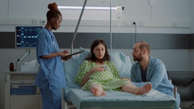 病棟の妊婦にタブレットを使用したアフリカ系アメリカ人の看護師。出産時に子供の父親と一緒に座っている赤ちゃんのバンプを持つ患者を期待しています。医療支援とのカップル