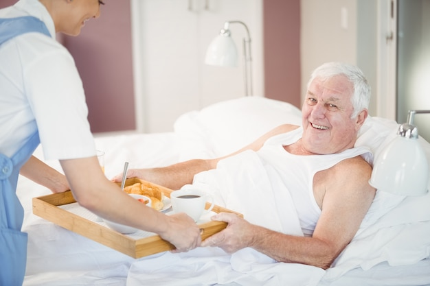 Nurse offering breakfast to senior man lying on bed