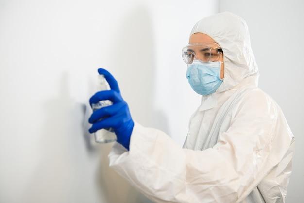 看護師または医師の防護服、ボトルから白い手の消毒剤。アルコール系スプレーの抗菌ジェル。コロナウイルス対策のコンセプト