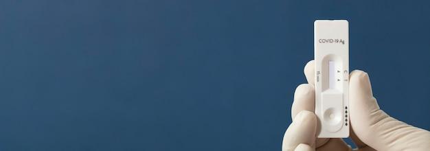 看護師または医師が青色の背景で抗原検査を行います