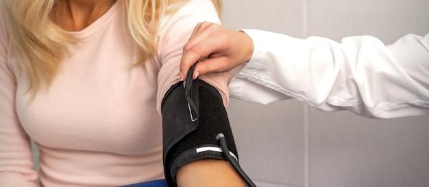 Медсестра или женщина-врач надевает тонометр на руку молодой женщины в больнице