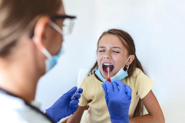 어린 아이에게 구강 면봉 검사를 수행하는 간호사. covid-19 전염병으로 인해 pcr 검사를 받는 소녀. 작은 소녀를 pcr 테스트하는 동안 면봉을 사용하는 여의사