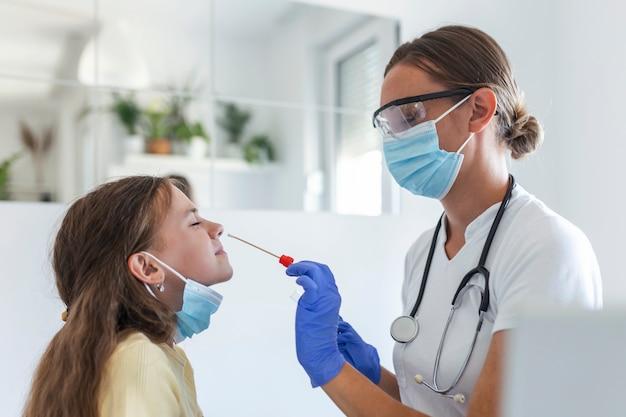 어린 아이에게 코 면봉 검사를 수행하는 간호사. covid-19 전염병으로 인해 pcr 검사를 받는 소녀. 작은 소녀를 pcr 테스트하는 동안 면봉을 사용하는 여의사