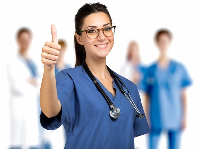 Nurse portrait full length giving thumbs up in front of a medical team