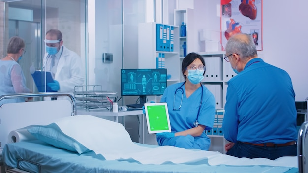 Nurse presenting green screen tablet to patient in modern private hospital. isolated mockup chroma replacement screen on gadget for your app, text, video or digital assets. easy keying medicine medica