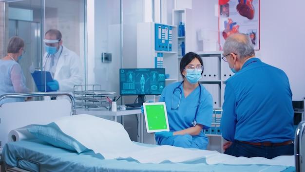 현대 사립 병원에서 환자에게 그린 스크린 태블릿을 제시하는 간호사. 앱, 텍스트, 비디오 또는 디지털 자산에 대한 가젯의 격리된 모형 크로마 교체 화면입니다. 이지키잉 메디카