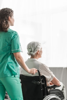 Nurse pushing disabled patient on wheel chair in hospital